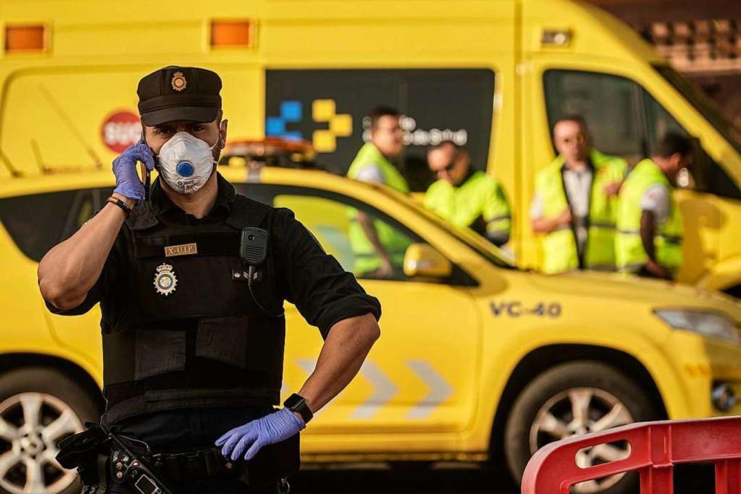 Ein Polizist mit Atemschutzmaske telef...t an einem Kontrollpunkt vor dem Hotel    Foto: Str (dpa)
