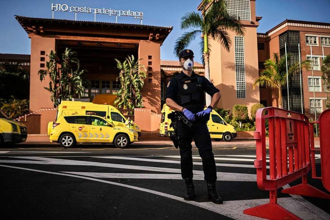 Ein Polizist mit Atemschutzmaske steht an einem Kontrollpunkt vor dem Hotel  | Foto: Str (dpa)