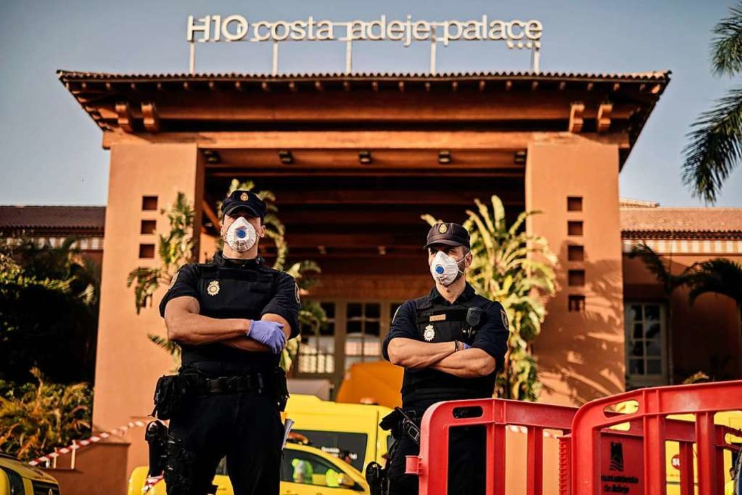 Polizisten mit Mundschutz stehen an einem Kontrollpunkt vor dem Hotel    Foto: Str (dpa)