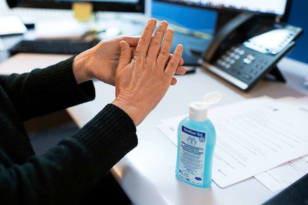 Ein Büroangestellter desinfiziert sich die Hände wegen der Coronakrise.  | Foto: Christian Beutler