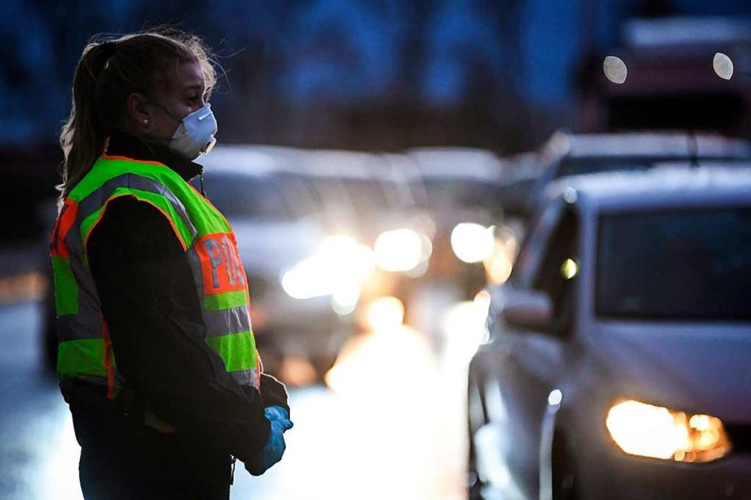 Eine Polizistin mit Mundschutz führt i...en an der Grenze zu Deutschland durch.  | Foto: Patrick Hertzog (dpa)