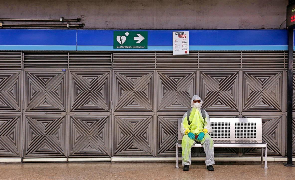 Ein Mann in Schutzkleidung sitzt in einer U-Bahnstation in Madrid.  | Foto: Guillermo Santos (dpa)