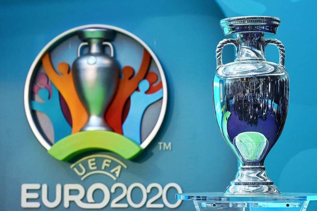 Der EM-Pokal neben dem Logo für die UEFA EURO 2020.  | Foto: Facundo Arrizabalaga (dpa)