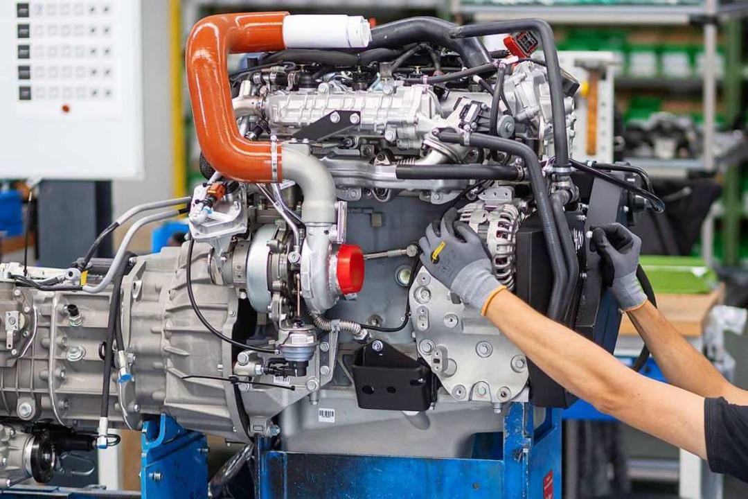 Ein Mann montiert in der Fertigung eines Unternehmens einen Motor.  | Foto: Michael Reichel (dpa)