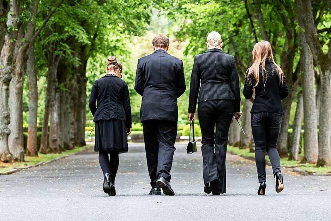 Trauernde Menschen laufen über einen Friedhof.    Foto: Kzenon (stock.adobe.com)
