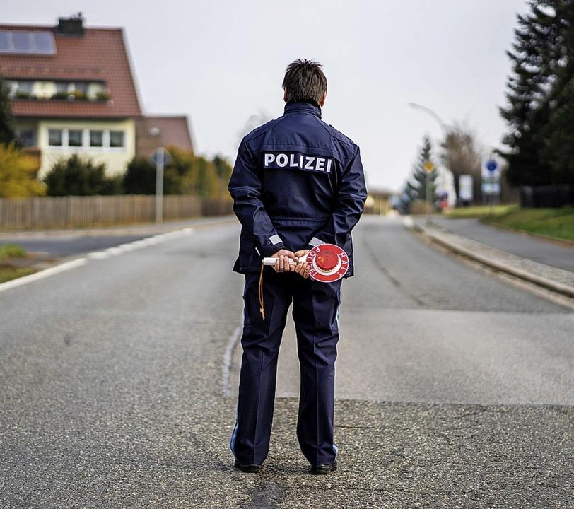 Ein Polizist kontrolliert die Ortseinfahrt von Mitterteich in Bayern   | Foto: Nicolas Armer (dpa)