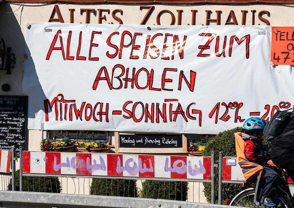 """""""Alle Speisen zum Abholen"""" b...großen Plakat neben der Eingangtür an,    Foto: Frank Rumpenhorst (dpa)"""