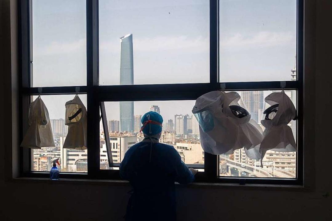 Es ist die Stadt, in der die globale P...m auf Wuhan, neben ihm Schutzkleidung.    Foto: STR (AFP)