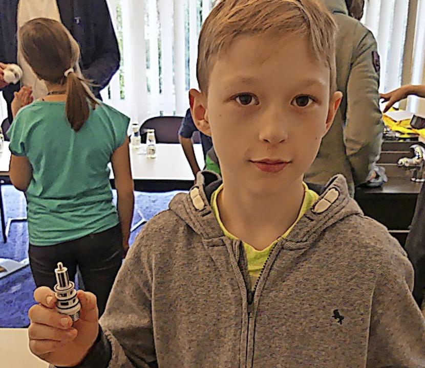 Severin Schumacher hält einen  Umsteller für Wannenarmaturen in der Hand.  | Foto: Saskia Bührer