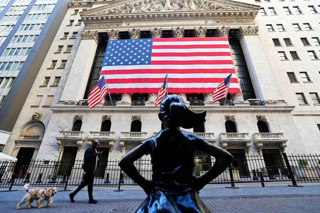 An der Vorderseite der New Yorker Börse hängt eine US-Flagge.  | Foto: Wang Ying (dpa)