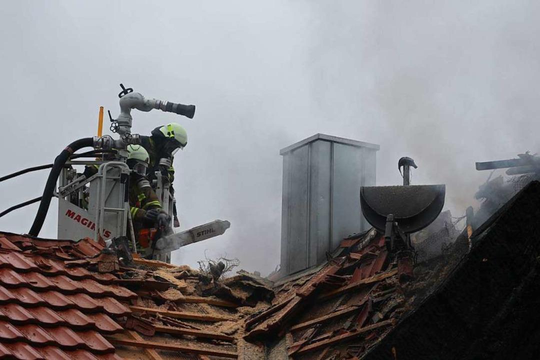 Feuerwehrleute decken das Dach des Woh...Dachstuhl unter Kontrolle zu bekommen.  | Foto: Alexander Huber