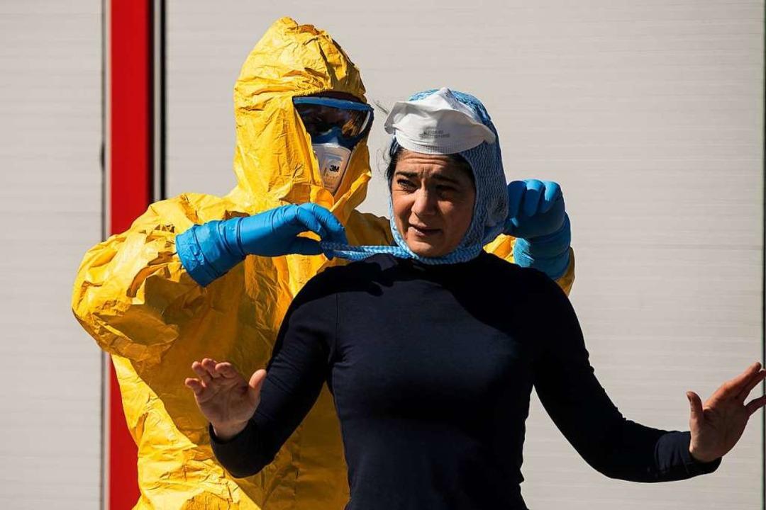 Ein Feuerwehrmann hilft am Euroairport...n Covid-19-Patient ausgeflogen wurde.     Foto: SEBASTIEN BOZON (AFP)