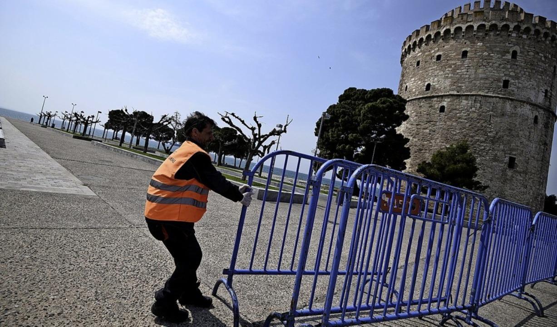 In Thessaloniki errichtet ein Stadtarbeiter eine Straßensperre.  | Foto: Giannis Papanikos (dpa)