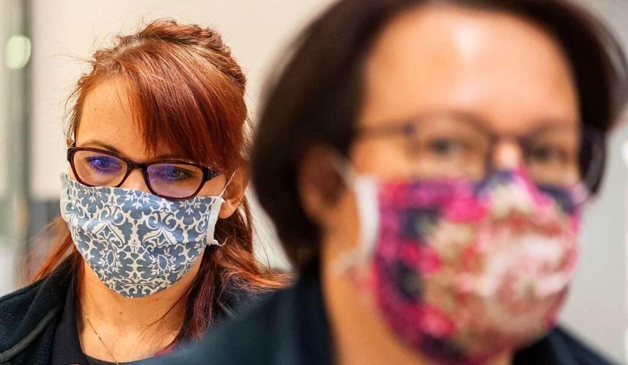 Trägt man eine Schutzmaske, kann die G...dere anzustecken, etwas geringer sein.  | Foto: Robert Michael (dpa)