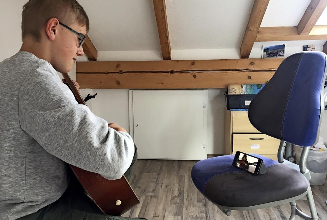 Simon Harder aus Lenzkirch bei einem Gitarrenunterricht via Handy.  | Foto: Ursula Harder