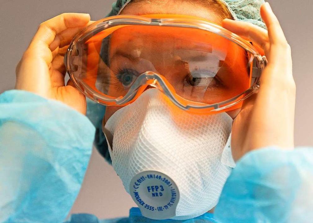 Eine Zahnmedizinische Fachangestellte ...FP3 Atemschutzmaske (gestellte Szene).  | Foto: Robert Michael (dpa)