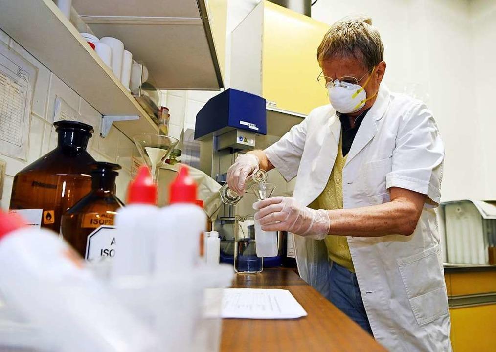 Apotheker Michael Hofheinz beim Abfüllen von Hände-Desinfektionsmittel.  | Foto: Uli Deck (dpa)
