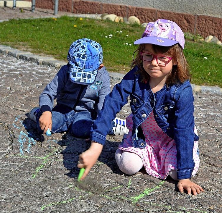 Die Kinder der Familie Wiemer zeichnen...d Kindergarten auf Straße und Gehweg.   | Foto: Liane Schilling
