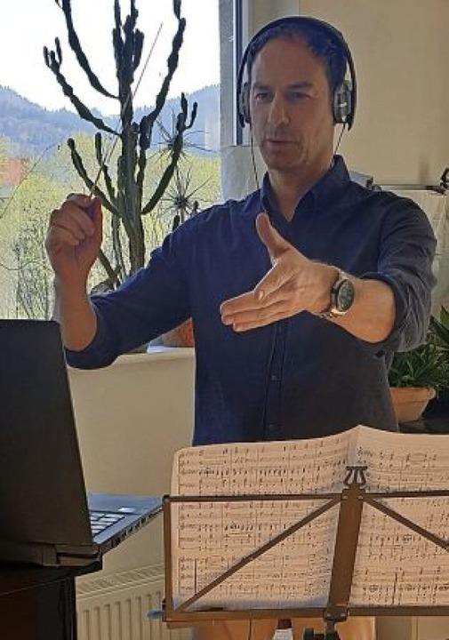 Jürgen Burmeister bei der Probe via In...p, Taktstock, Kopfhörer  und Partitur.  | Foto: Burmeister