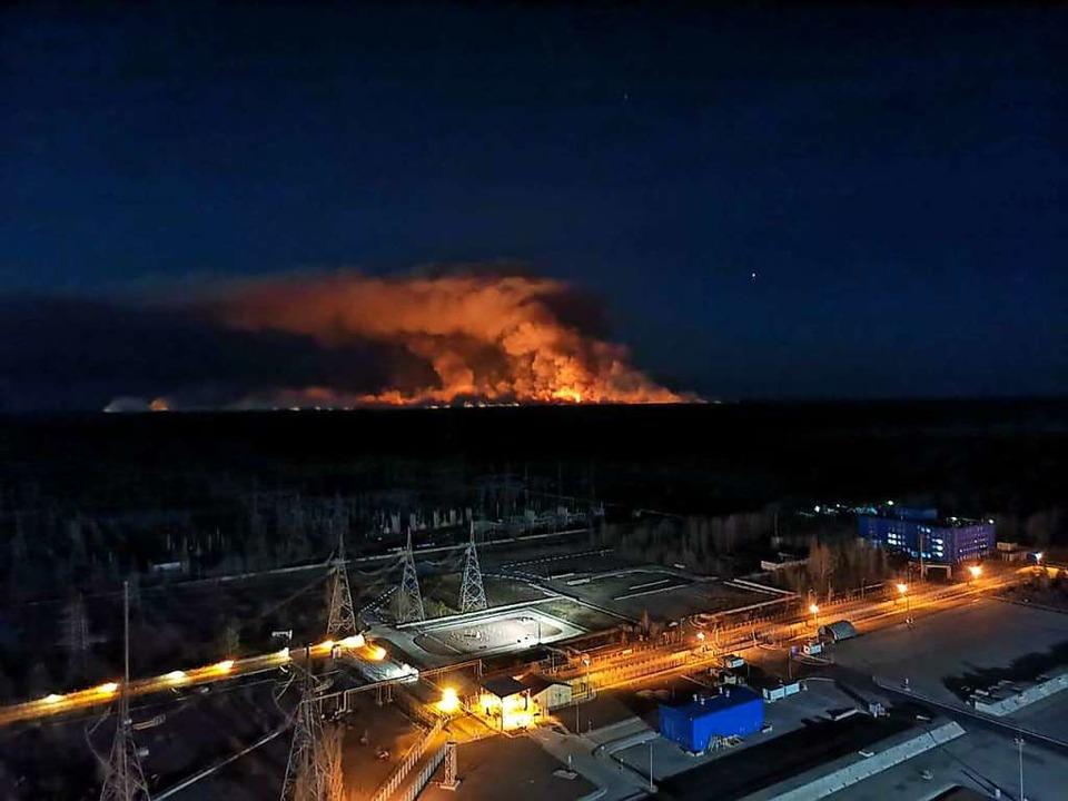 Am Horizont steigen Rauchschwaden von ... um das Kernkraftwerk Tschernobyl auf.  | Foto: Uncredited (dpa)