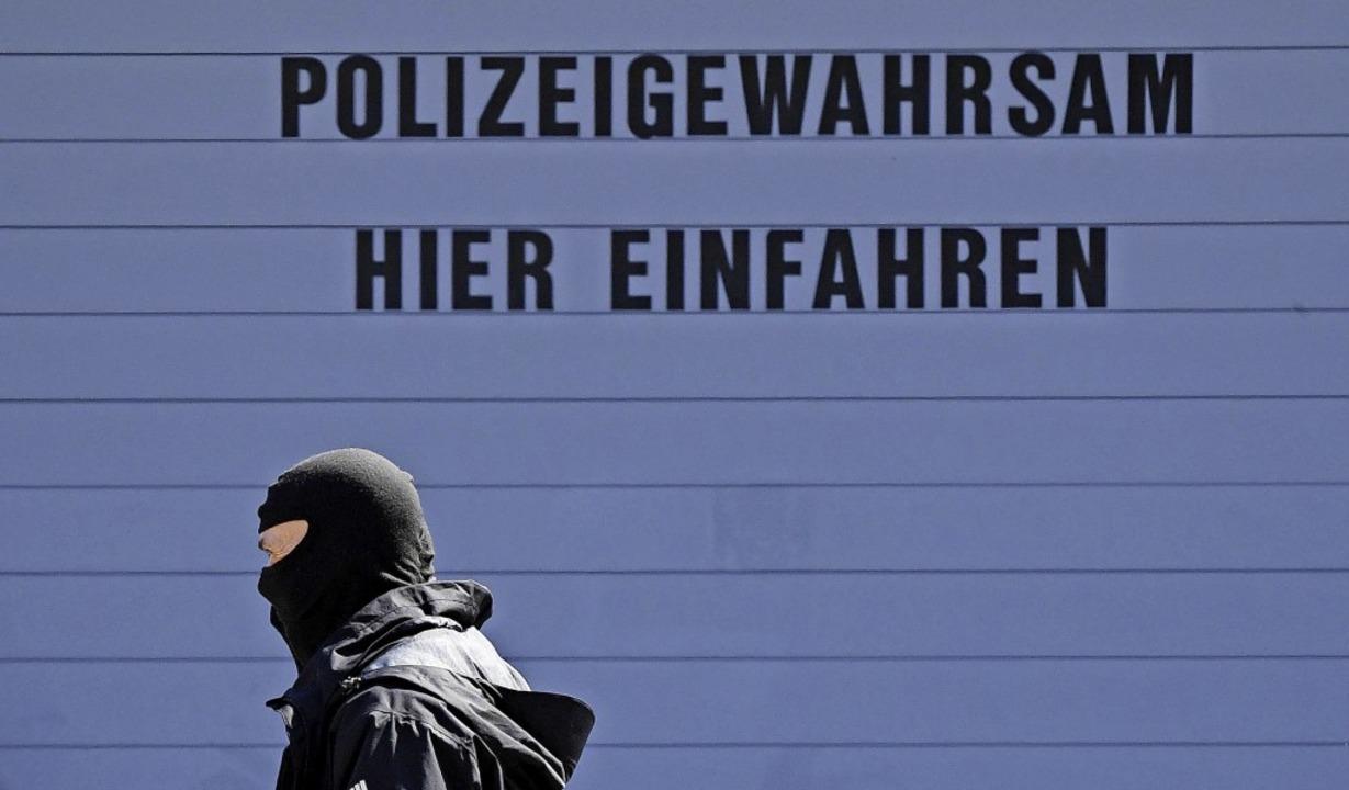 Ein maskierter Polizist  vor dem Bunde...gen dem Haftrichter vorgeführt wurden.    Foto: Uli Deck (dpa)