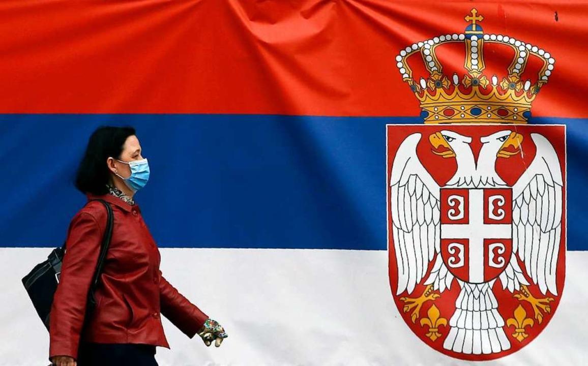 Belgrad: Eine Frau mit einem Mundschut...ationalflagge auf einer Straße vorbei.    Foto: Darko Vojinovic (dpa)