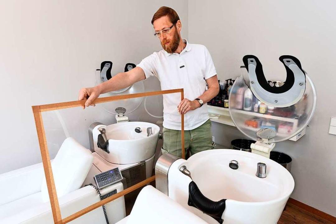 Friseur Günther Ducke testet eine Schutzvorrichtung für Waschbecken.  | Foto: Thomas Kunz
