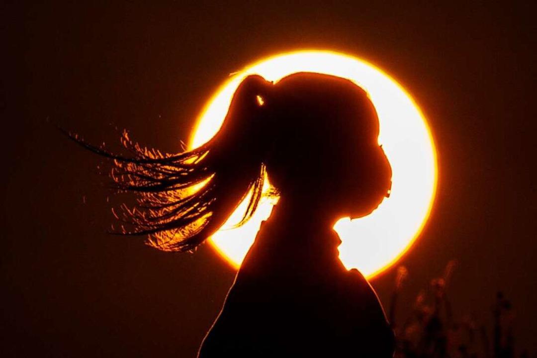 Sonnenuntergang mit Mundschutz genießen? Reiseromantik geht irgendwie anders.  | Foto: Hassan Ammar (dpa)