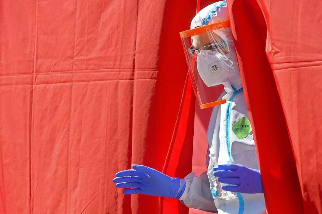 Ein medizinischer Mitarbeiter im Schut...-19-Tests vor einem Krankenhaus steht.  | Foto: Slavomír Kubeš (dpa)