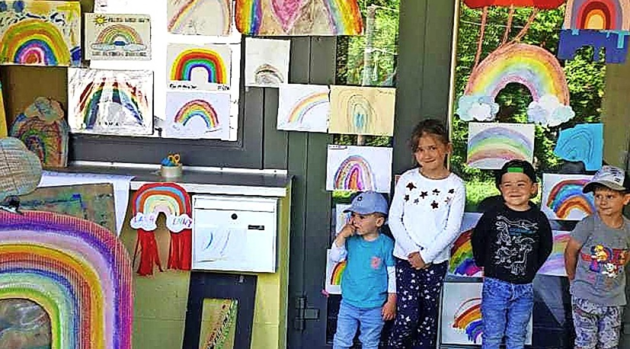 Kinder aus der Notbetreuungsgruppe am ...en mit den gemalten Regenbogenbildern.  | Foto: Cecile Buchholz