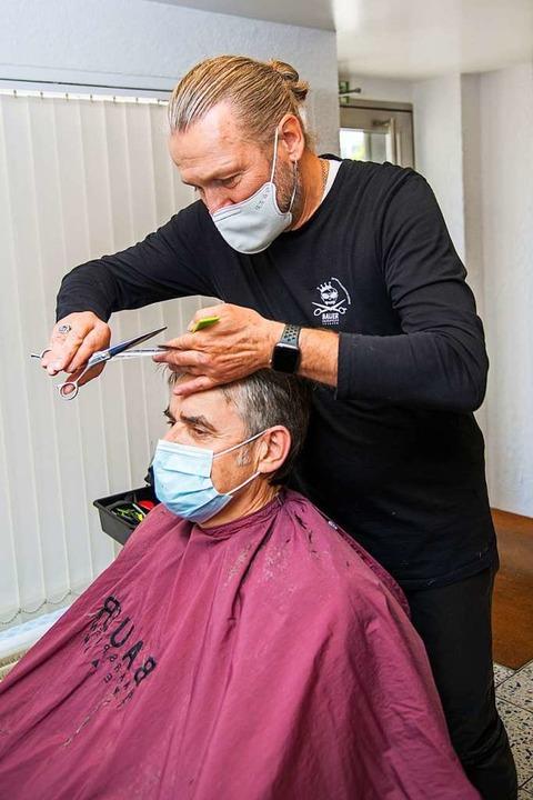 Kunde und Friseur müssen Mundschutz tr...ordnung. Joachim Bauer bei der Arbeit.  | Foto: Olaf Michel