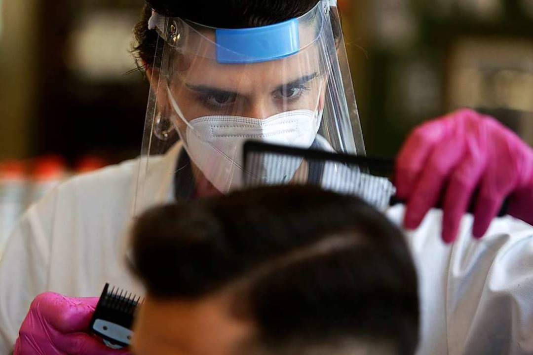 Friseurin mit Mund- und Nasenschutz  | Foto: Armando Franca (dpa)