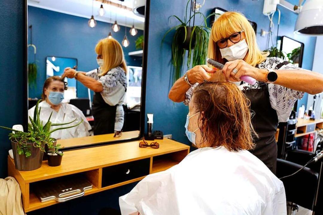 Friseure dürfen wieder Haare schneiden – allerdings unter strengen Regeln.  | Foto: VALERY HACHE (AFP)