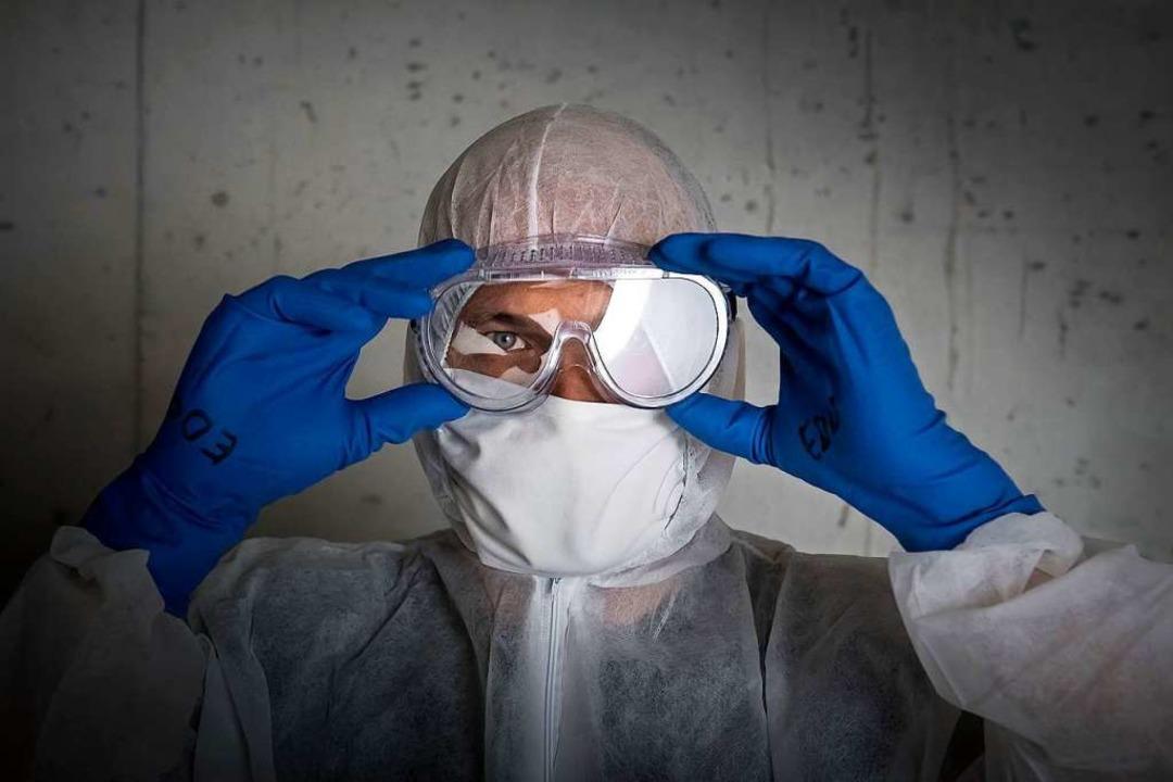 Ein Mann in Schutzkleidung rückt seine Brille zurecht.  | Foto: Pablo Gianinazzi (dpa)