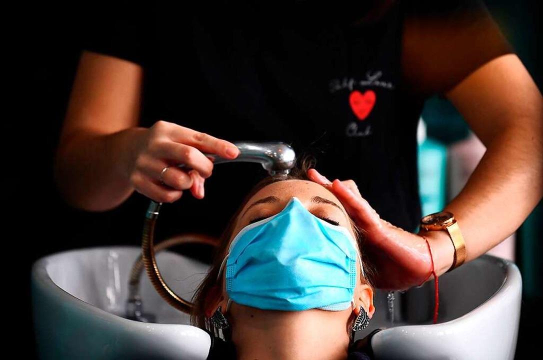 Natürlich mit Mundschutz lässt sich di...schwester in Paris ihre Haare waschen.  | Foto: FRANCK FIFE (AFP)