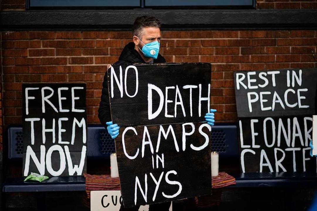 Ein Mann protestiert vor einem New Yor...id-19 Erkrankten in den Einrichtungen.  | Foto: JOHANNES EISELE