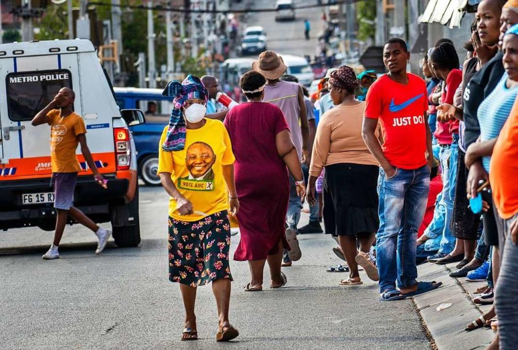 In Johannesburg trägt eine Frau mit Mu...den Wirtschaft des Landes vorgeworfen.  | Foto: Jerome Delay (dpa)