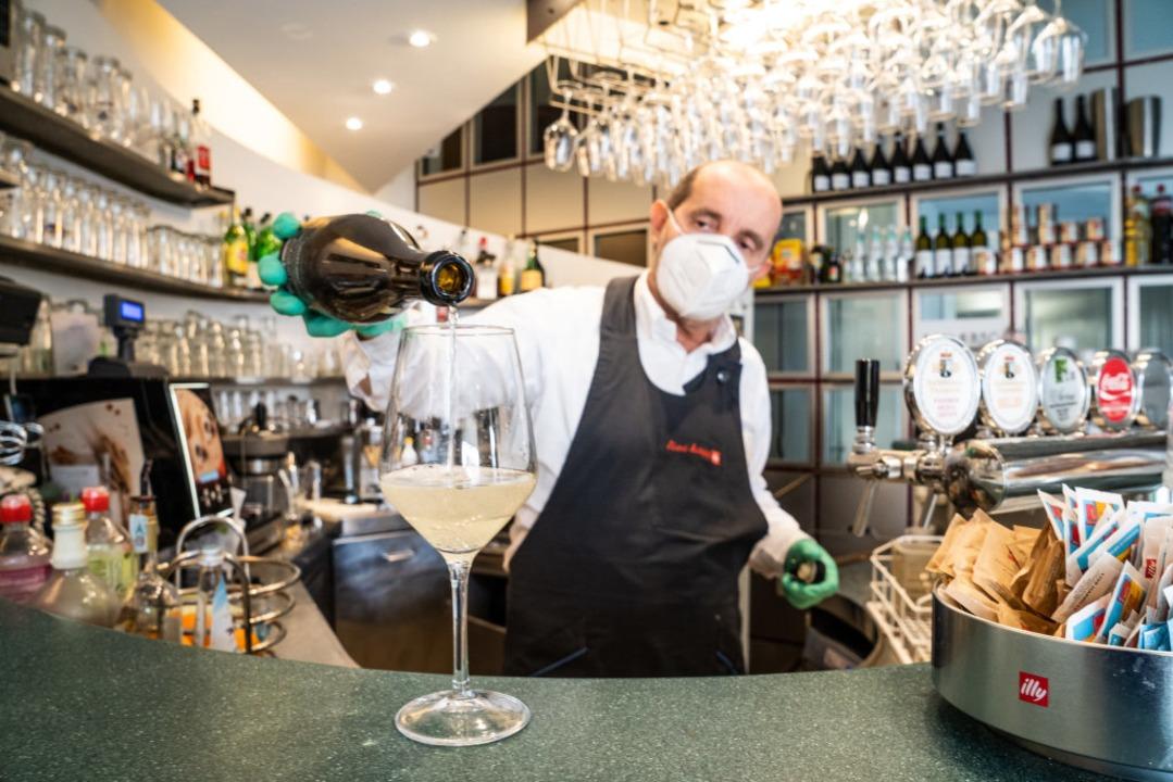 Ein Barmann mit Atemschutzmaske arbeitet in einer Bar in Bozen hinter der Theke.  | Foto: Matteo Groppo (dpa)