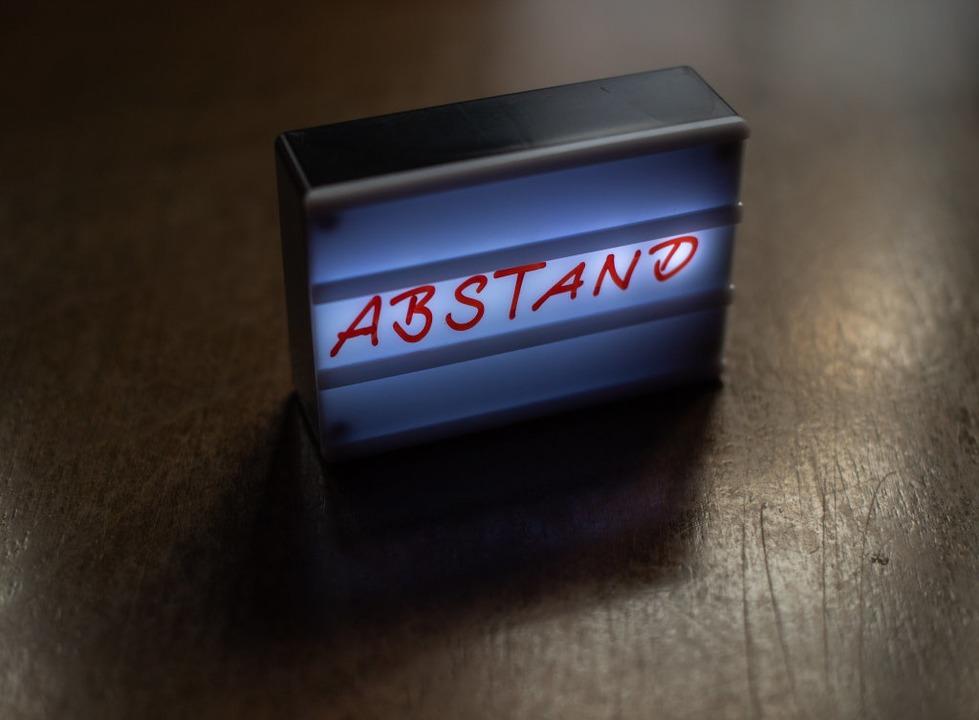 Ein beleuchtetes Schild mit der Aufsch...tand steht auf einem gesperrten Tisch.  | Foto: Robert Michael (dpa)