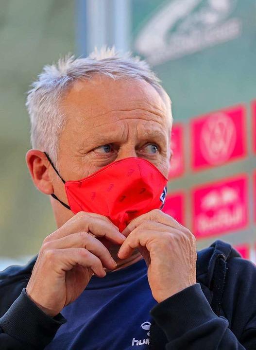 Christian Streich mit Vereinsmaske    Foto: Jan Woitas (dpa)