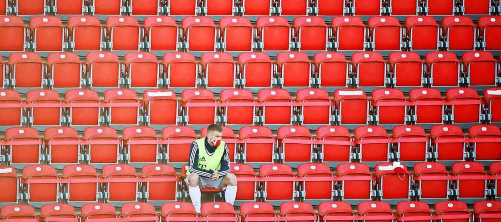 Bayern-Ersatzspieler Lukas Mai sitzt a...sterei in Berlin und trägt eine Maske.  | Foto: Hannibal Hanschke (dpa)