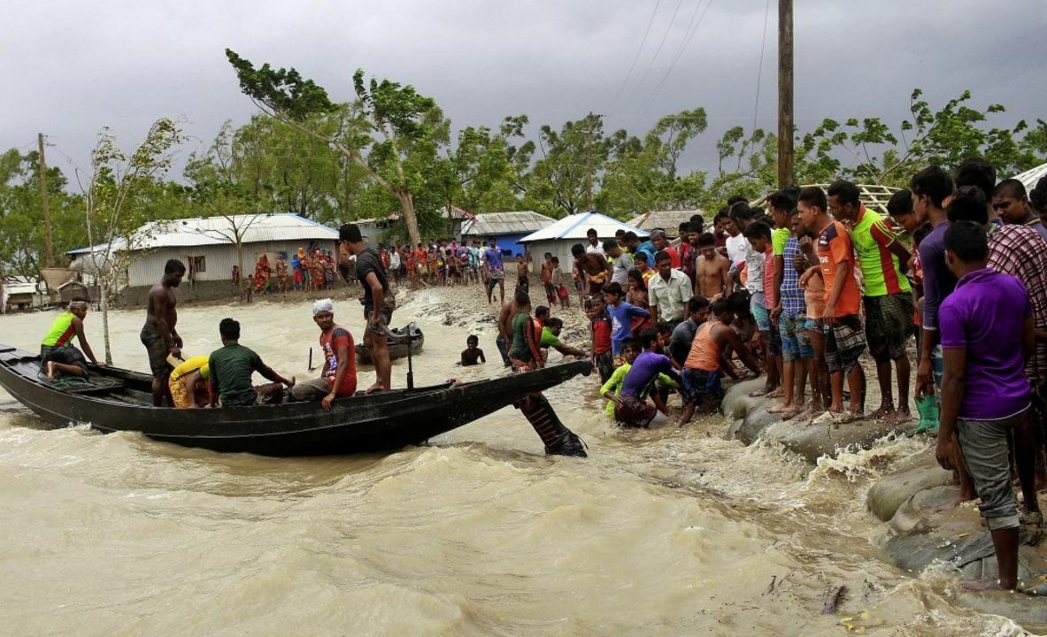 Ein Boot bringt  Menschen im indischen...nd Einheimische einen Damm überprüfen.  | Foto: Abu Sufian Jewel (dpa)