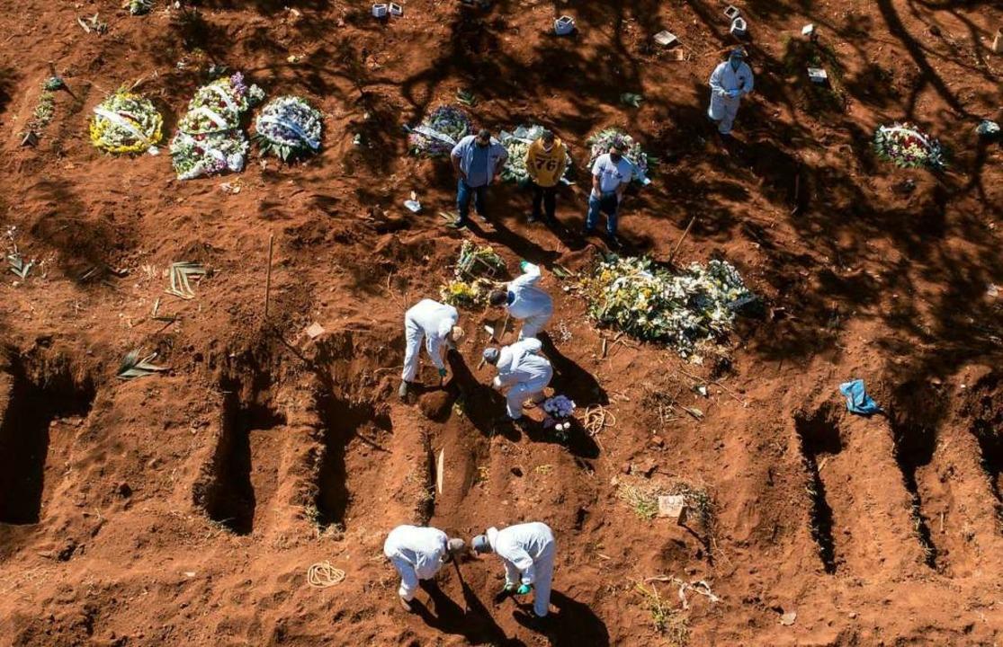 Angestellte in Schutzkleidung beerdige... Zusammenhang mit dem Virus gestorben.    Foto: Andre Penner (dpa)