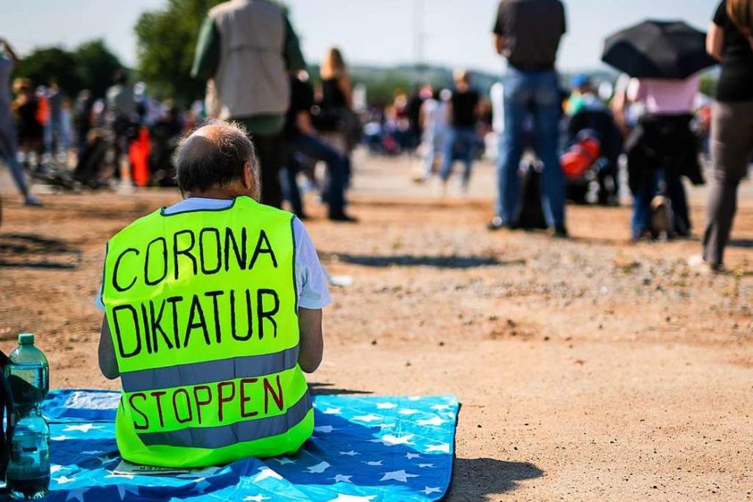 Ein Teilnehmer einer Demonstration in ...r wenige Menschen am heutigen Samstag.    Foto: Christoph Schmidt (dpa)