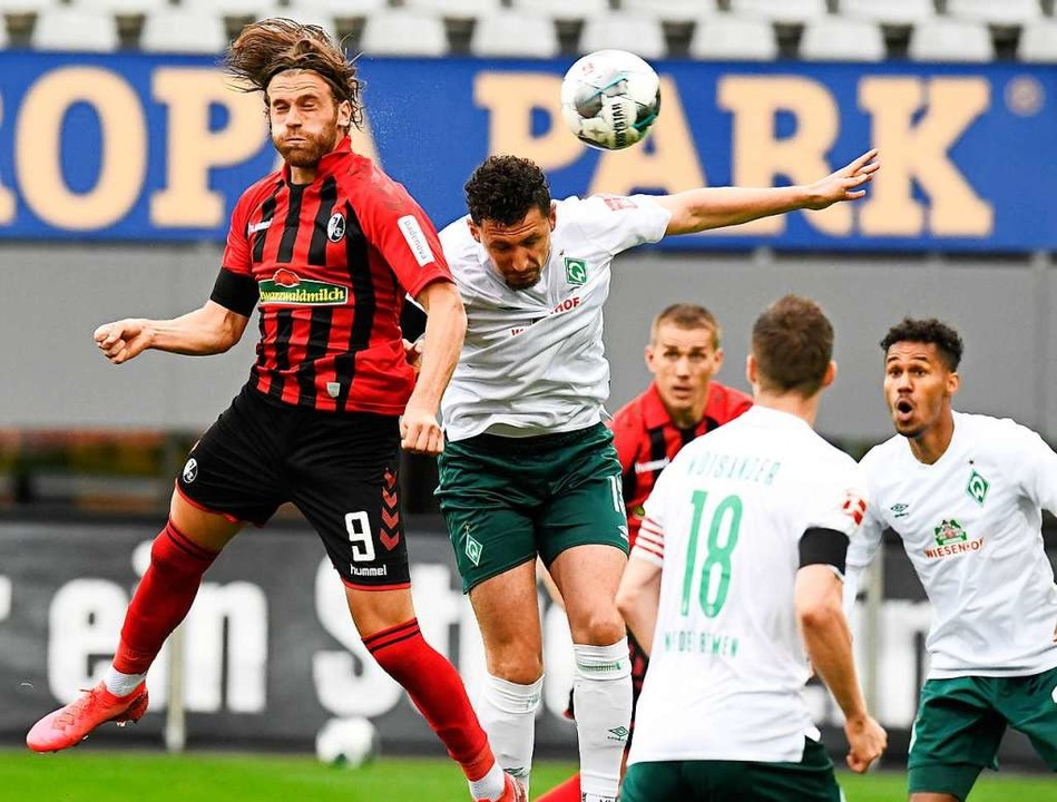 Lucas Höler mit dem Kopfballduell gegen seinen Bremer Konkurrenten.  | Foto: THOMAS KIENZLE (AFP)