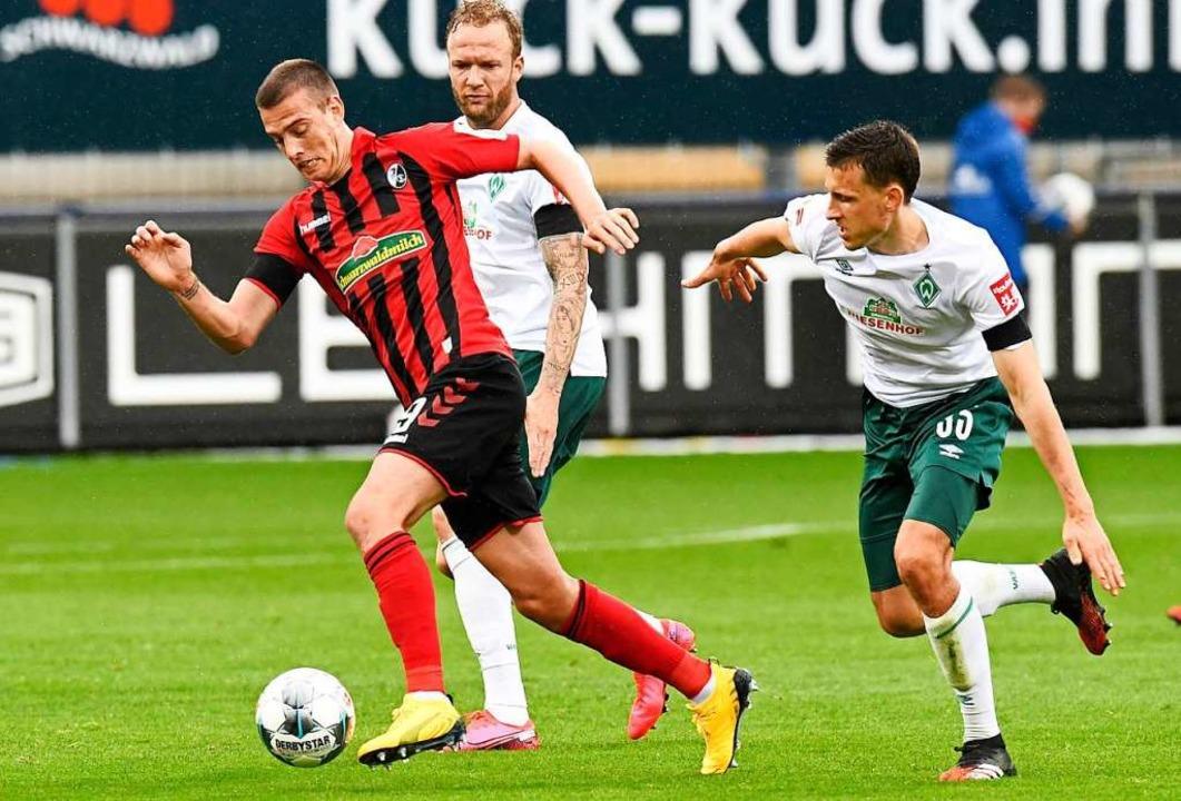 Janik Haberer zieht mit dem Ball am Fuß auf und davon.  | Foto: THOMAS KIENZLE (AFP)