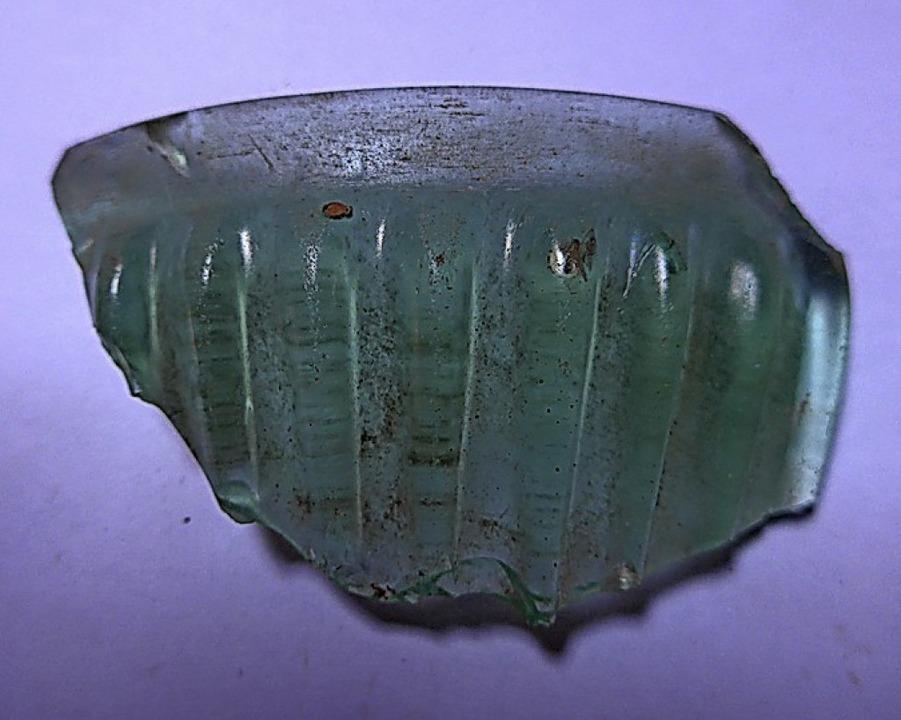 Ein Randstück einer Rippenschale aus grünlichem Glas wurde  ebenfalls gefunden.   | Foto: Archaeo Task