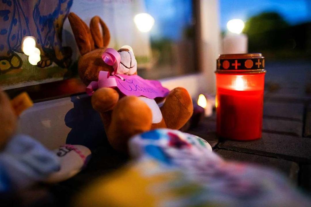 Stofftiere und Kerzen liegen vor dem E...n ein dreijähriges Kind getötet haben.    Foto: Marcel Kusch (dpa)