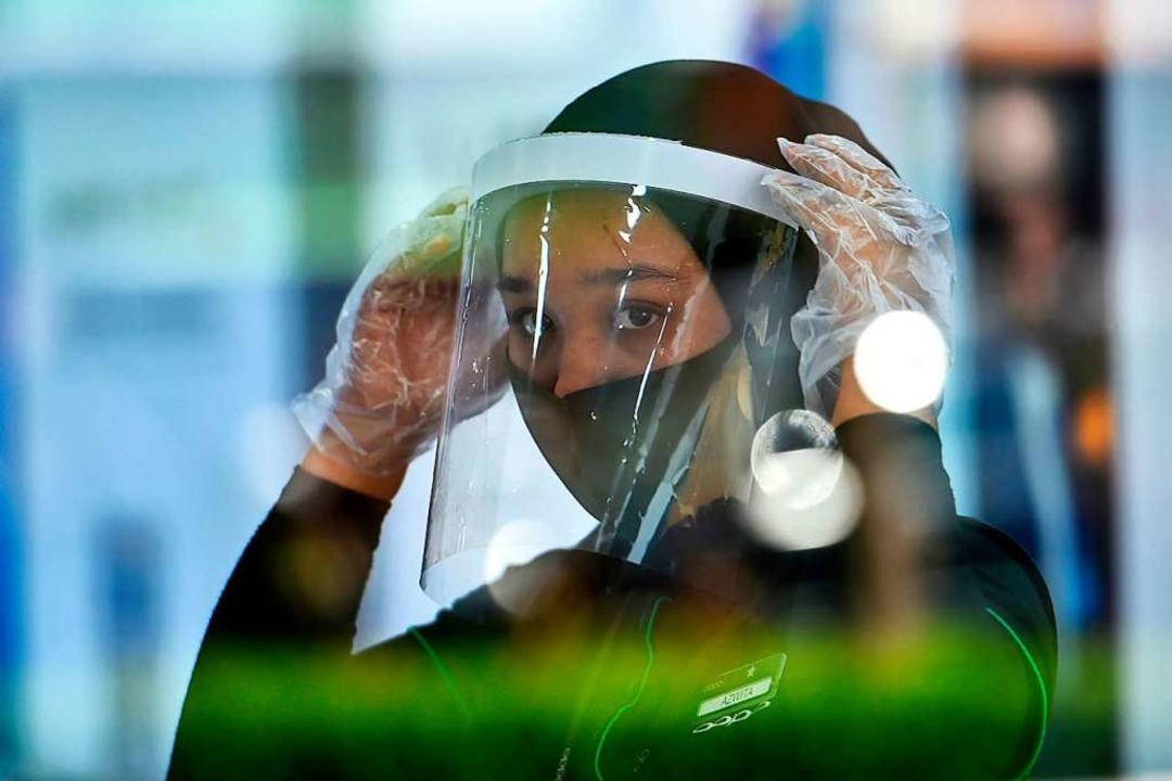 In der Corona-Krise schützen die Menschen sich und andere mit Masken.  | Foto: CHAIDEER MAHYUDDIN (AFP)