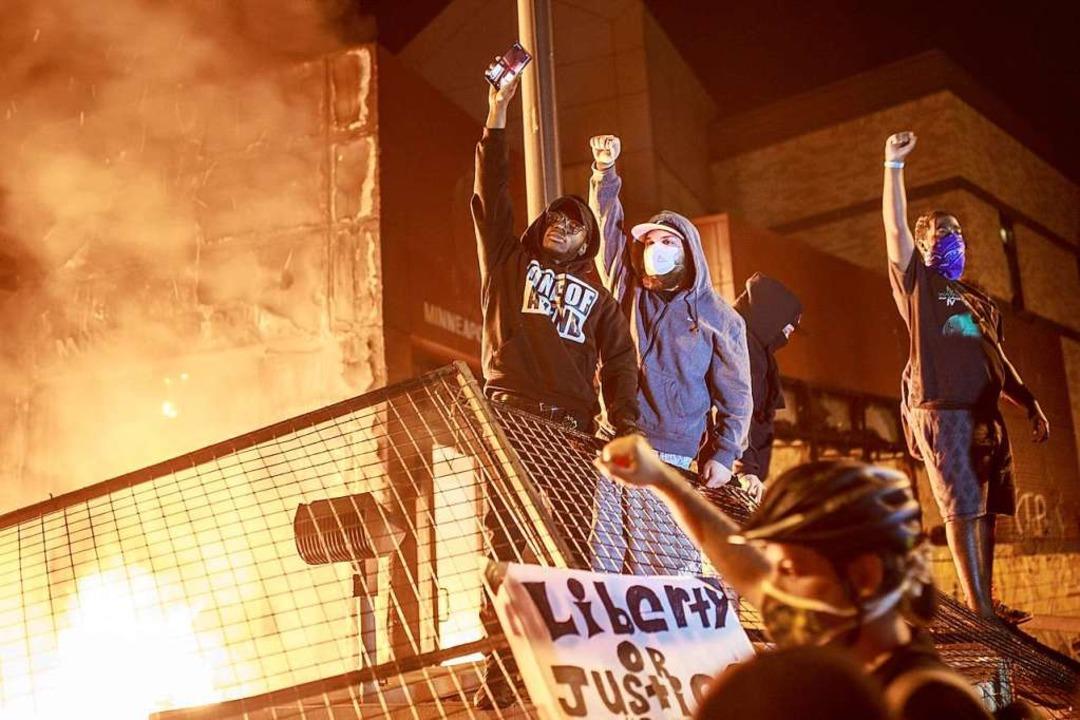 Protestanten vor der brennenden Polizeistation.  | Foto: KEREM YUCEL (AFP)